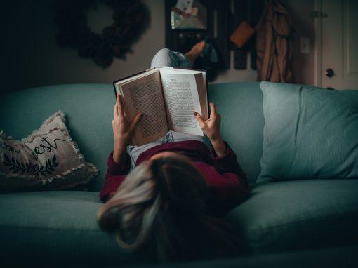 Foto de Matias North. Moça deitada lendo livro em sofá verde.