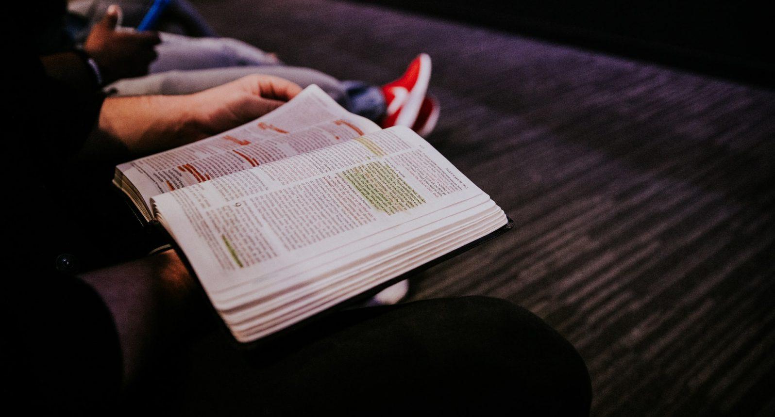 Pessoa segurando bíblia. Foto de Hannah Busing no Unsplash